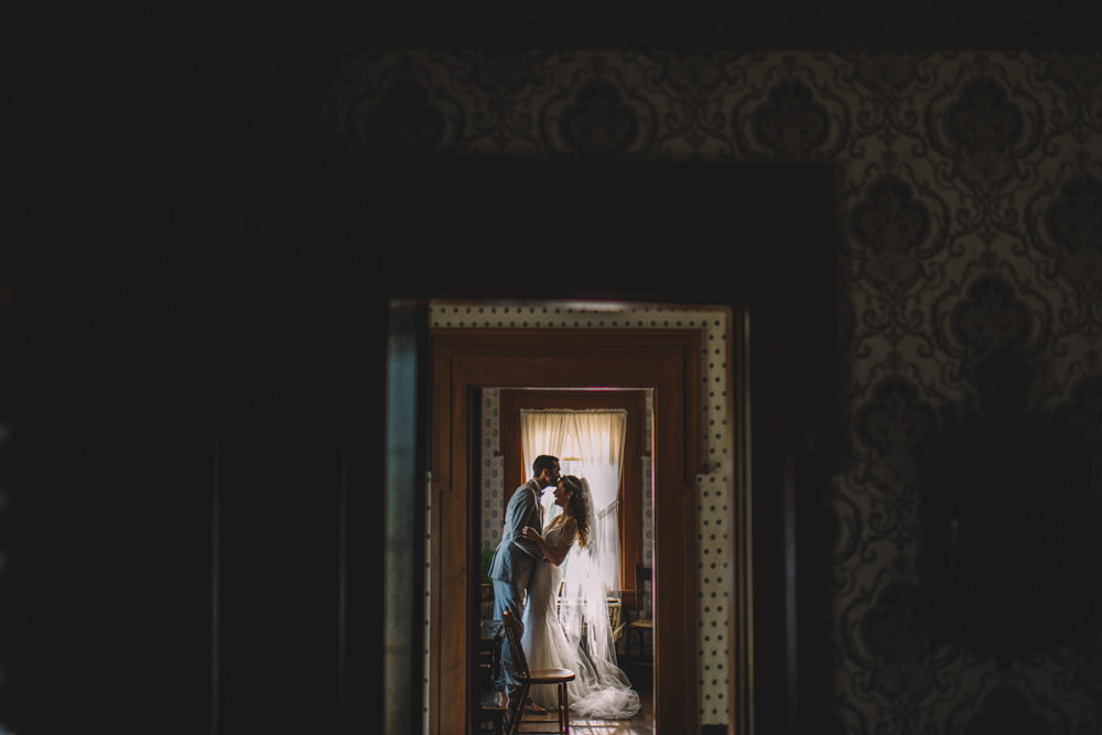 couple sharing a quiet moment in a farmhouse on their wedding day