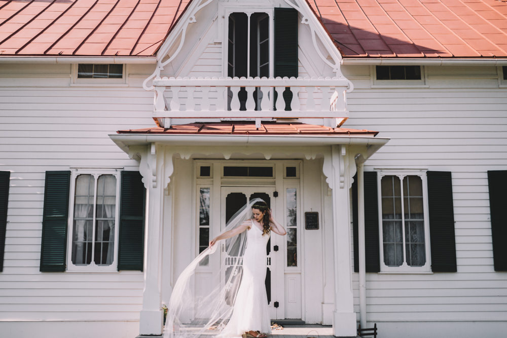 bride fixing her veil in front of a farmhouse in columbus ohio