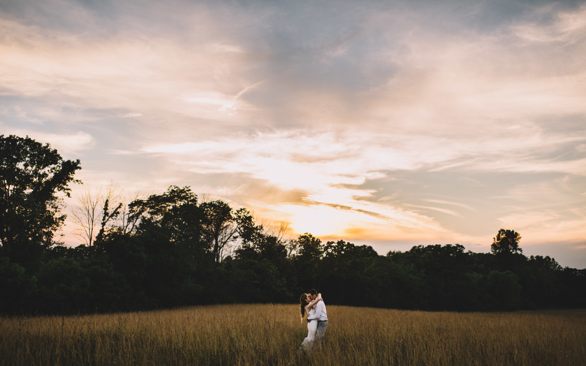 columbus ohio couple kissing in a field at sunset