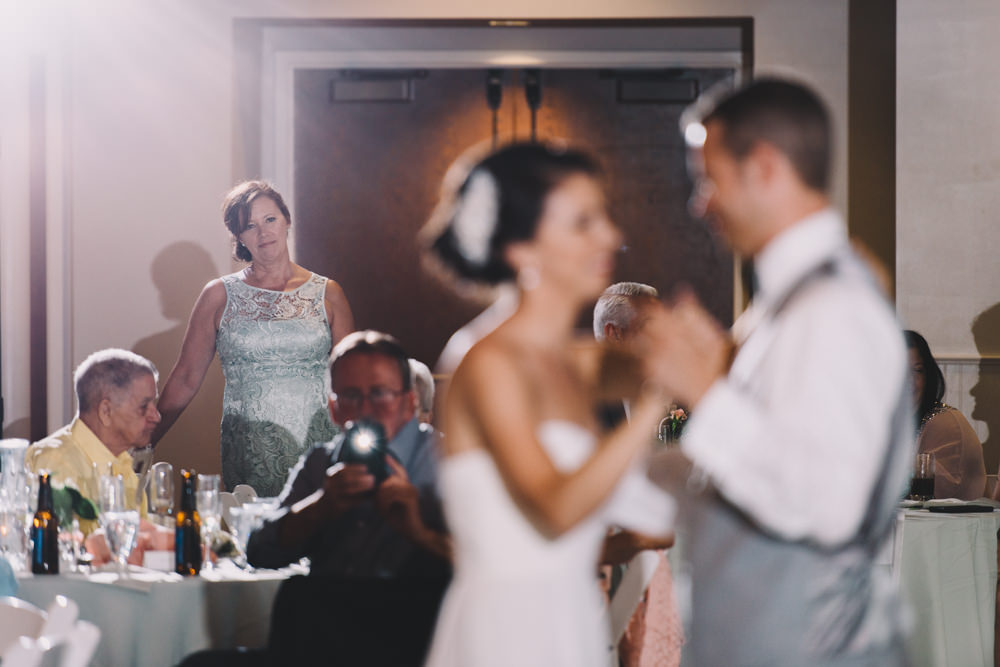 mom looking on at her daughter during her wedding first dance