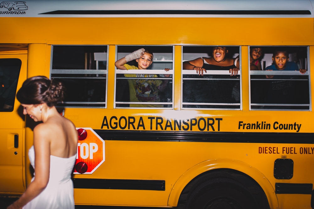 kids in a school bus waving at a columbus bride and groom