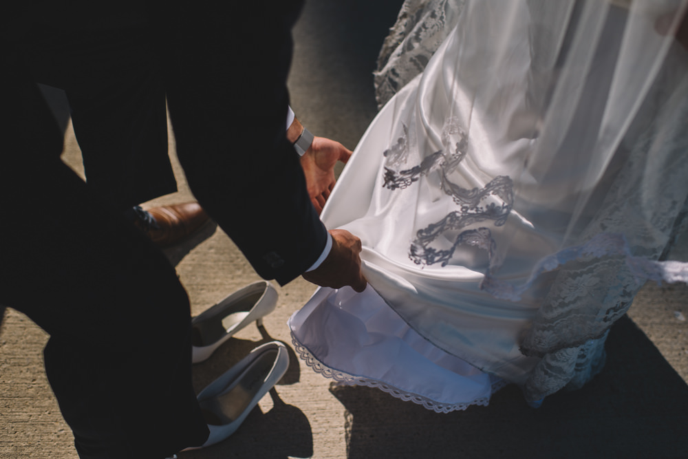 groom helping fix his bride's wedding dress