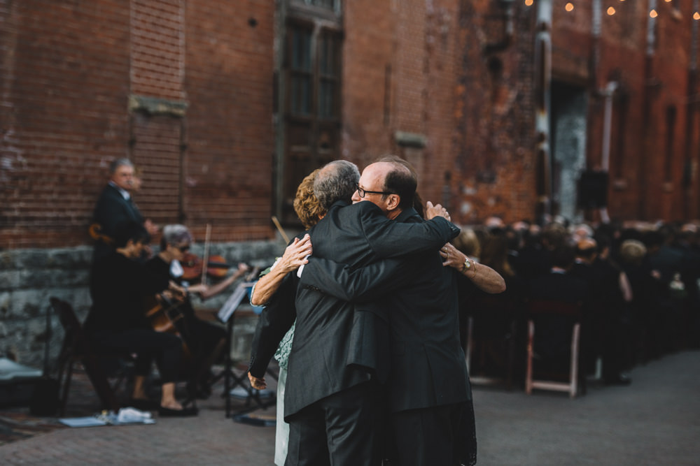 bride and groom's parents hugging each other after a via vecchia winery jewish wedding